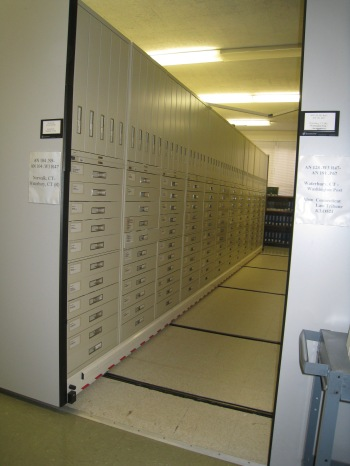 There are several rows of newspaper microfilm in a back room.
