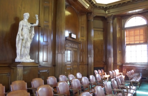 Blind statue of Justice facing the judges in the courtroom.