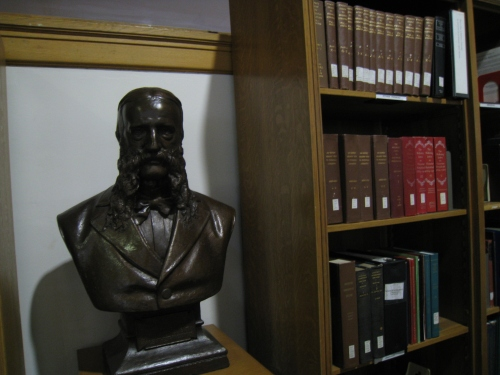 A bust of Poole next to his Index on the top shelf