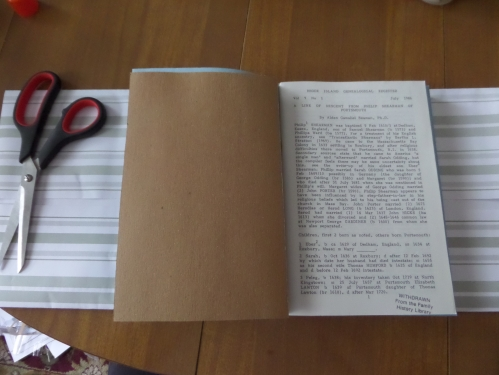 Folding the top and bottom of the paper sheet according to the size of the journal.  Adding the cardboard sheet.