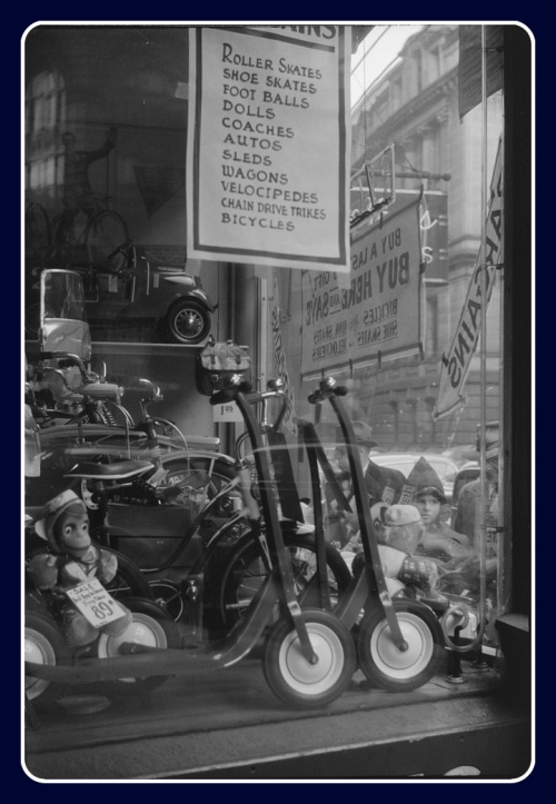 R.I. Cycle Co., a view of people looking in the window.