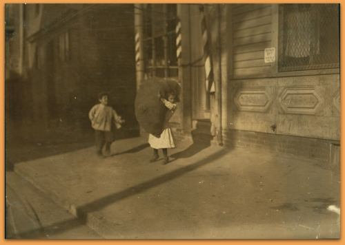 Tiny girl with big bag she is carrying home, Spruce St., Providence, R.I. Location: Providence, Rhode Island. LC-DIG-nclc-04300 (color digital file from b&w original print)