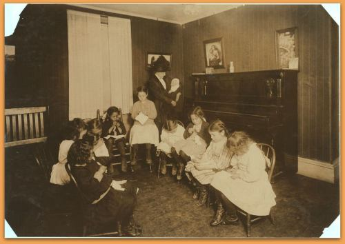 Sewing class in Sprague House Settlement Providence, R.I. The Director is holding a newly-arrived deserted baby. Location: Providence, Rhode Island. LC-DIG-nclc-04795 (color digital file from b&w original print)